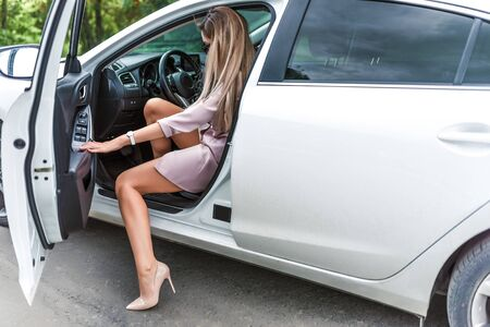 Woman gets out of car, summer in city, white business class car. Car rental, stylish and fashionable girl in high heels. Long hair tanned figure. VIP taxi, car sharing. Free space for copy text