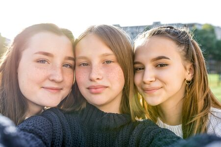 Three teenage girls of 12-14 years old, summer city watching videos phone, happy smiling people having fun rejoice. Selfie portrait close-up. Casual clothes, sweaters. Emotions of positive relaxation