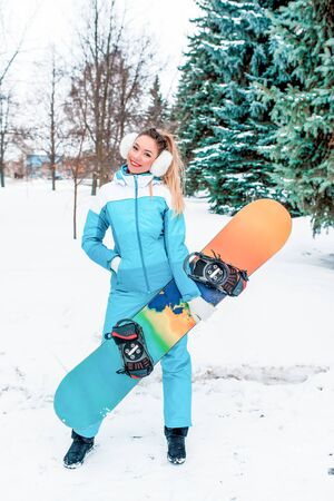 Beautiful girl in winter on nature holding snowboard board. Sports jumpsuit. Snowboard background snow, Christmas trees. Emotions joy, fun, pleasure enjoyment winter resort Stock Photo