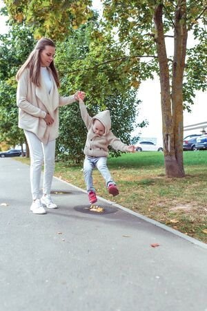 Young family, woman mom, holding her sons hand, little boy jumping puddle, walk in park, concept parenting care and support parent love. Free space for copy text. Background trees and asphalt
