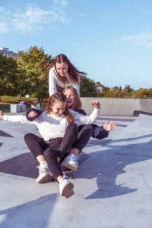 3 Young girls teenage schoolgirls ride skateboard summer park. Casual wear sweater jeans. Emotions happiness, fun, relaxation, smile laughter, best girlfriends, rest after college.