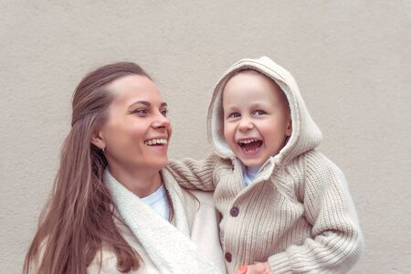 Happy family, woman mom, holds her arms, little son boy, autumn. Emotions fun joys laughter smile. Casual warm clothes hood. Background beige wall, child care parenting. Positive delight celebration