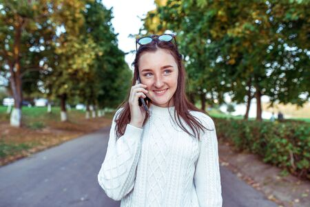happy girl smiles rejoices, teenager, phoning smartphone hand, listening voice message, online application Internet. Social networks. Rest in weekend. Emotions of happiness, joys fun pleasure