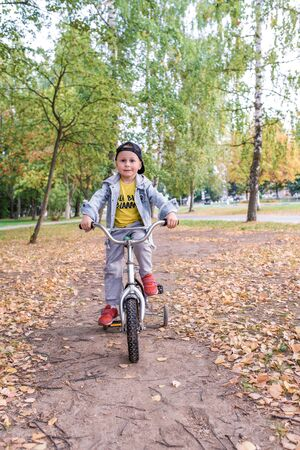 Little boy 3-5 years old, summer park, background trees. Trains learns keep balance bicycle, rides pedals. In summer in city, emotions interest comfort happiness. Casual wear, denim baseball cap