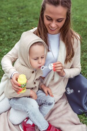 Happy woman mom, little boy plays inflates soap bubbles, casual warm clothes hood. Autumn day summer on grass. Weekend breaks, caring parenting childcare. Emotions Happiness joy fun smile Banco de Imagens