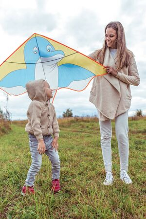 Happy family woman mom and little boy son fly kite, summer autumn day in field. Emotions of happiness, fun, joys of laughter and smile