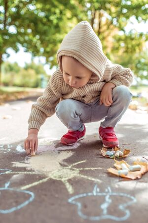 little boy, casual clothes, beige sweater hood, autumn day in summer in city, draws sun on asphalt with colorful chalks. Creative concept idea and creativity. Background green trees