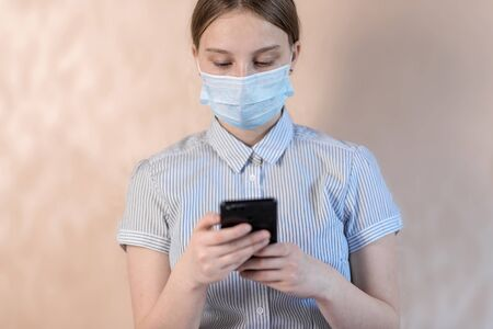 Teenager girl, protective mask, writes message on smartphone, online video Internet application, anti-coronavirus COVID-19 pandemic infectious disease outbreak protection healthcare concept