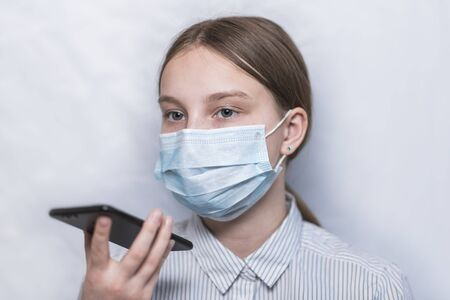teenager girl of 11-14 years old, protective medical mask, records voice message smartphone, online application, talking remotely with parents, communicating Internet. Flu infection disease pandemic.