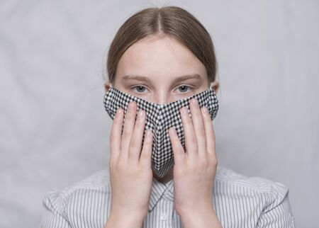 Close-up portrait, teenage girl of 14 years old, mask, holds mask with his palms, safety and prevention of influenza covid-19 diseases and infections in pandemic. In medical mask on white background.