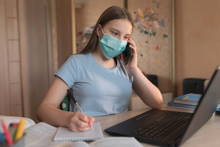 teenager girl in a medical mask, calls on phone, writes task in notebook, online home training video on Internet, a laptop with the Internet. Distance education during quarantine, stay at home. Stok Fotoğraf
