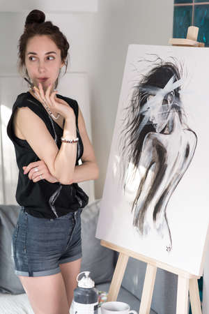 beautiful girl in hands paintbrush, happy looks model poser, draws silhouette of woman, painting easel. Home in workshop. Emotions of fantasy, enjoyment creativity and inspiration. Art painting Standard-Bild