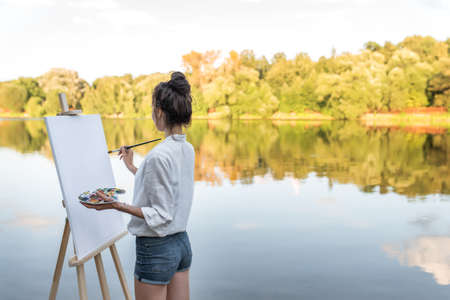 girl artist summer shore lake river, free space for text, background water forest trees, begins draw picture, in hand palette with paints, brush easel. Clothes white shirt shorts. White blank canvas