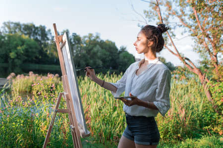 beautiful girl artist in summer on shore of lake and river, background forest trees, draws a picture, in her hand a palette with paints brush and easel. Clothes white shirt shorts. Hair in a bun