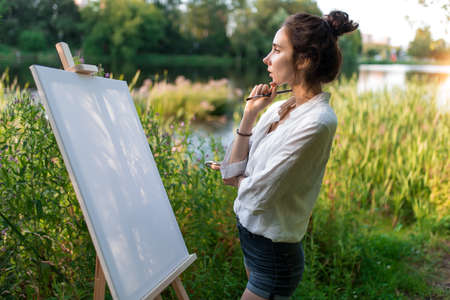 beautiful girl artist in summer on shore lake and river, background forest trees, fantasizes dreams, looks at white canvas painting, in hand brush and easel. Clothes white shirt shorts. Hair in bun.