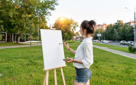 woman artist city summer, background car road, green lawn, begins paint picture on white canvas, hand brush color palette of paints, easel. Clothes white shirt shorts. Hair bun. Free space side view