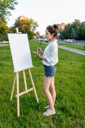 woman artist city summer, background car road, green lawn, begins paint picture on white canvas, hand brush color palette of paints, easel. Clothes white shirt shorts. Hair bun