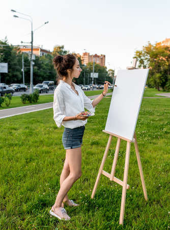 woman artist city summer, background car road, green lawn, begins paint picture on white canvas, hand brush color palette of paints, easel. Clothes white shirt shorts. Hair bun. Side view