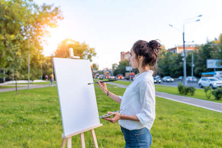 beautiful girl city summer, woman artist, draws picture road, beginning of drawing, first brush stroke, white canvas painting, easel stand. Green grass lawn background, cars on highway. Hair in bun Banque d'images