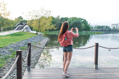 woman in summer in a city park near a reservoir, a pond, river and lake, records video photos on a smartphone. Sightseeing and travel. Back view. Denim shorts jacket with backpack