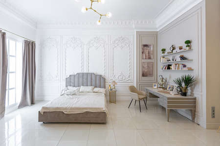 chic luxury interior in an old antique style open-plan apartment decorated with columns and stucco on the wall in pastel colors. tiles on the floor. beige walls Banque d'images