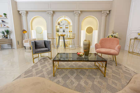 chic luxury interior in an old antique style open-plan apartment decorated with columns and stucco on the wall in pastel colors. tiles on the floor. beige walls