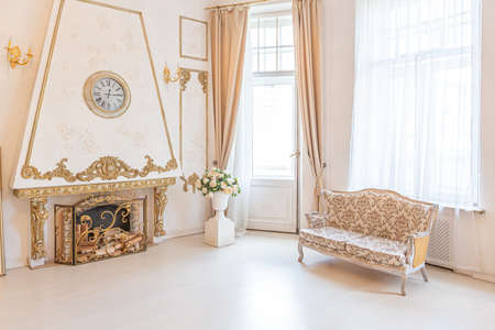 luxurious expensive interior of a large baroque royal living room. antique furniture, gold trim, huge windows, fireplace with gold stucco on the walls. full of daylight Archivio Fotografico