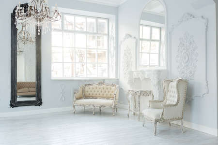 Luxury rich living room interior design with elegant classic furniture and wall decorations. Large light white room with big window