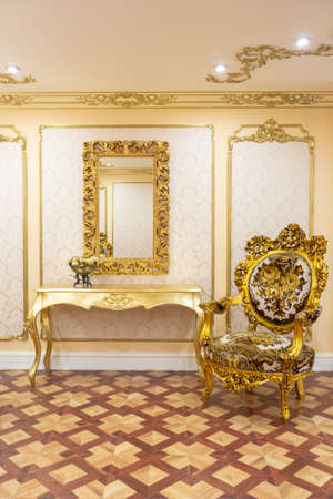 luxurious living room interior with beautiful old carved furniture of gold color with decorations on the walls in the style of the royal palace