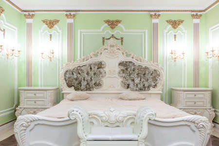small luxury bedroom with bath and expensive furniture in a chic old baroque style.