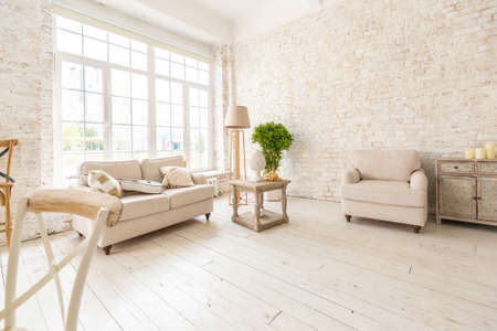 Large spacious room with a trendy loft design of sitting area. huge windows and stylish wicker light furniture inside. an abundance of ethnic decor Stock fotó