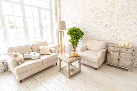 Large spacious room with a trendy loft design of sitting area. huge windows and stylish wicker light furniture inside. an abundance of ethnic decor Reklamní fotografie