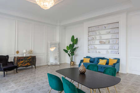 modern and very stylish interior design of large studio apartment with fashionable furniture with gold elements. very light and bright room with big windows
