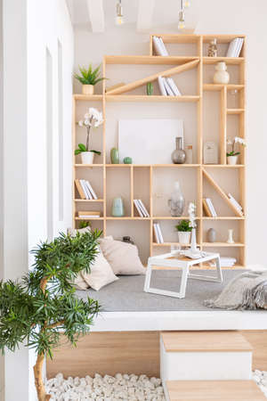 Luxury fashionable modern design studio apartment with a free layout in a minimal style. very bright huge spacious room with white walls and wooden elements. Stock Photo