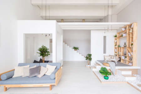 Luxury fashionable modern design studio apartment with a free layout in a minimal style. very bright huge spacious room with white walls and wooden elements.