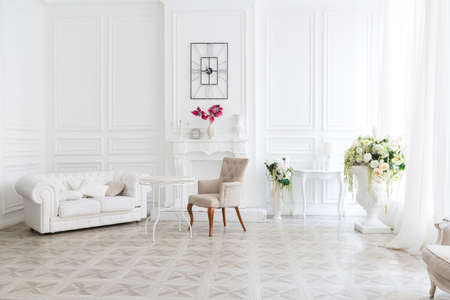 Luxury white interior of living spacious room with elegant chic furniture and high windows.