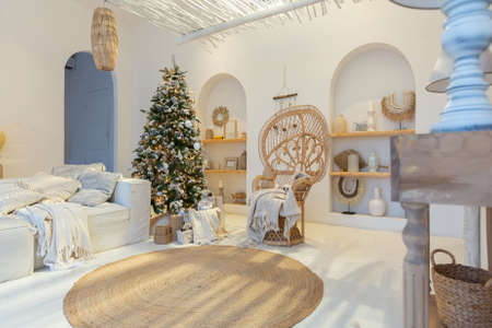 Cozy interior of a bright Balinese-style apartment with completely white walls, wicker furniture. sitting room full of day light decorated with Christmas tree