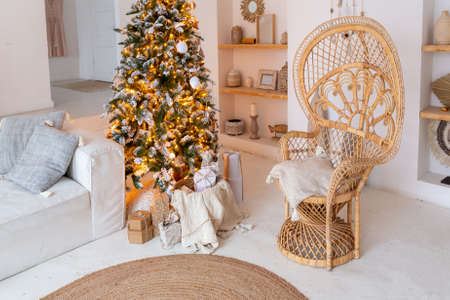 Cozy interior of a bright Balinese-style apartment with completely white walls, wicker furniture. sitting room full of day light decorated with Christmas tree Stock fotó
