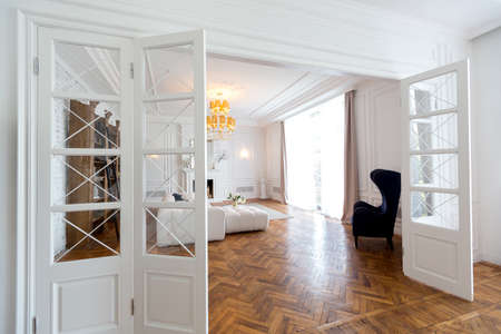 modern interior of a luxurious large bright two-room apartment. white walls, luxurious expensive furniture, parquet flooring and white interior doors