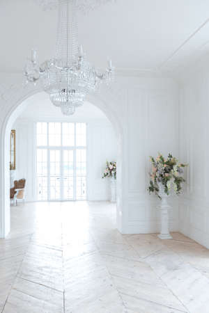 chic white huge spacious hall with a minimum of expensive antique furniture. Baroque interior design with ornament on the walls and parquet on the floor.