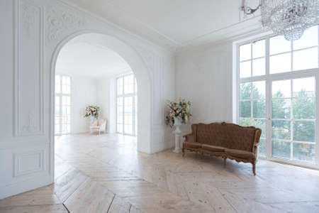 chic white huge spacious hall with a minimum of expensive antique furniture. Baroque interior design with ornament on the walls and parquet on the floor. Banco de Imagens