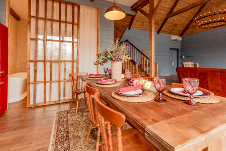 cozy all wooden interior of a country house in a wooden design. spacious living room with kitchen area with large windows. bedroom on the second floor. Banque d'images