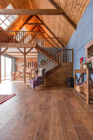cozy all wooden interior of a country house in a wooden design. spacious living room with kitchen area with large windows. bedroom on the second floor. Archivio Fotografico