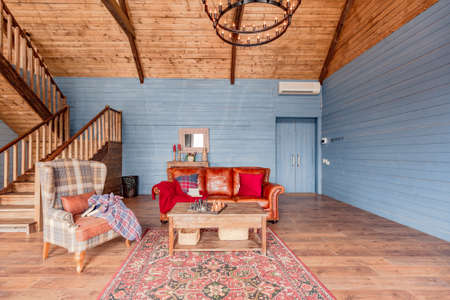 cozy all wooden interior of a country house in a wooden design. spacious living room with kitchen area with large windows. bedroom on the second floor.