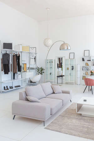 Cozy luxury modern interior design of a studio apartment in extra white colors with fashionable expensive furniture in a minimalist style. white tiled floor, kitchen, relaxation area and workplace