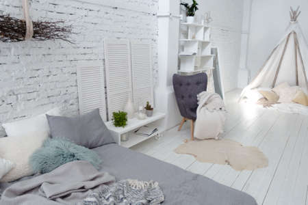 Spacious stylish modern trendy loft apartment in white and light colors. a large room full of sunlight. brick wall, wood floor, shelving, pallet bed and huge window. everything is white with gray tints. Stock Photo