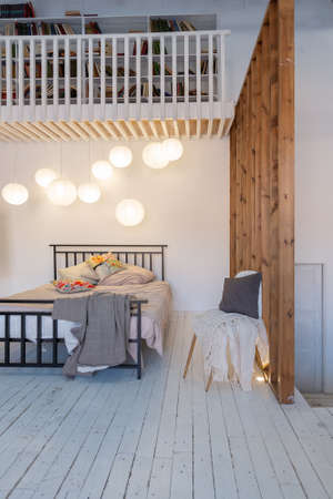 luxury modern design of a cozy small Scandinavian-style studio apartment with white walls, second floor with a library and huge high window full of day light Imagens