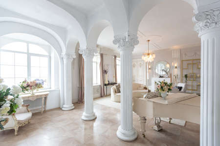 rich luxurious interior of a cozy room with modern stylish furniture nd grand piano, decorated with baroque columns and stucco on the walls Stock fotó