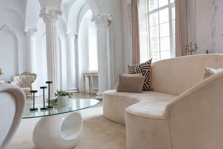 rich luxurious interior of a cozy room with modern stylish furniture nd grand piano, decorated with baroque columns and stucco on the walls