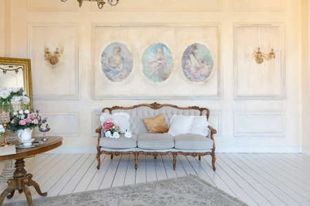 luluxe rich sitting room interior in beige pastel color with antique expensive furniture in baroque style. walls decorated with stucco and frescoes